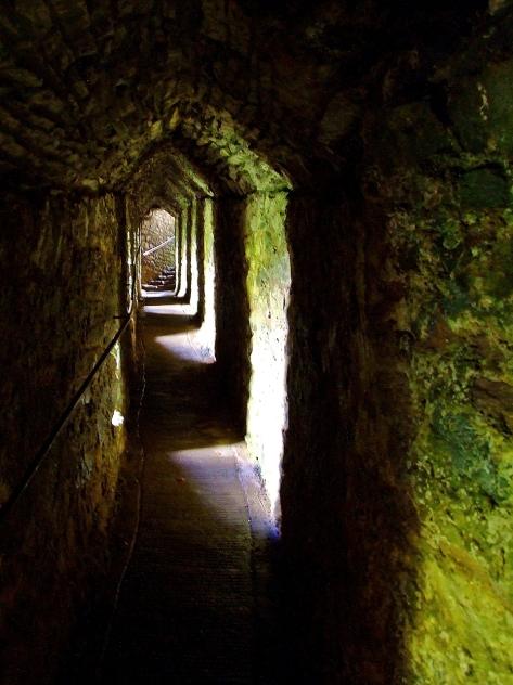 Wykuty w skale korytarz prowadzący do naturalnej jaskini pod zewnętrznym dziedzińcem zamku